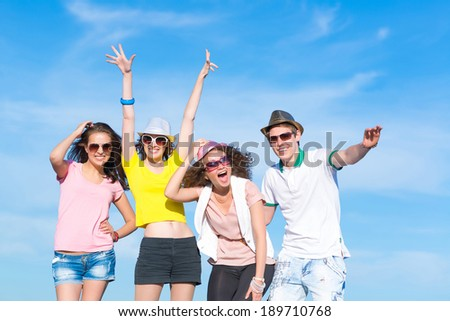 Group of young people having fun on a blue summer sky - stock photo