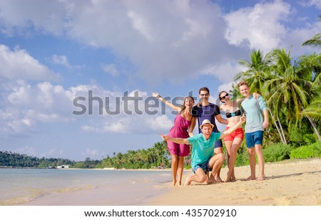 Group of young people having fun on the beach together. Vacation with friends. - stock photo
