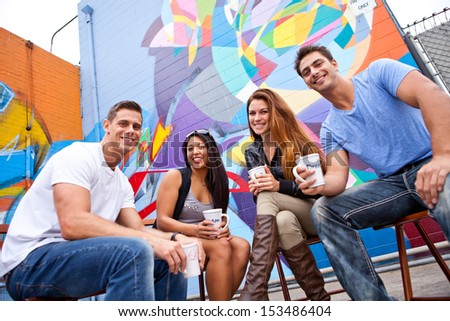 Group of young people in their twenties having Sunday Morning Coffee at an outdoor cafe - stock photo