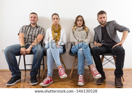 Group of young people is sitting in a row in an office lobby and waiting for the job interview.