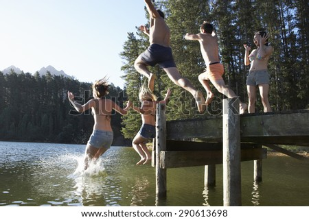 Group Of Young People Jumping From Jetty Into Lake - stock photo