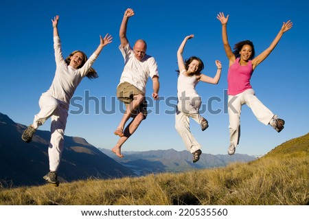 Group of young people jumping in the field. - stock photo