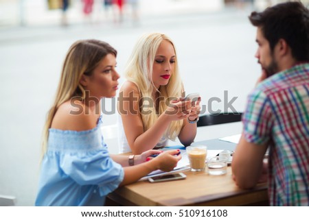 Group of young people laughing in cafe