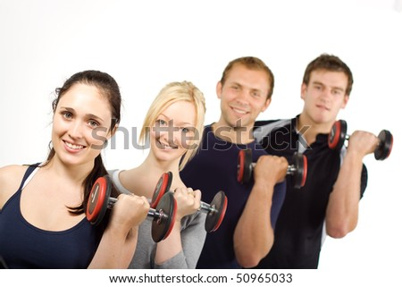 Group of young people lifting weights in the gym - stock photo