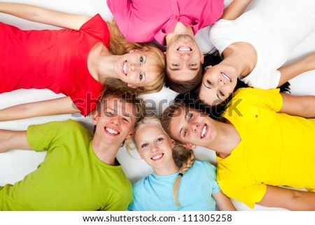 group of young people lying down on floor in circle, teenage students happy smile top angle view over white background - stock photo
