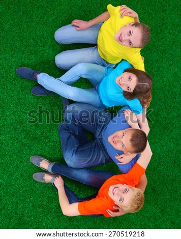 Group of young  people lying on green grass .