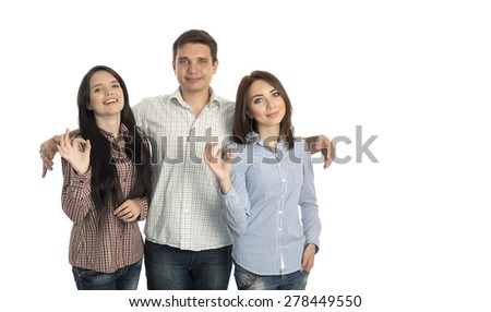 Group of young people makes OK gesture. Young man embracing two beautiful girls makes OK hand sign casual checkered shirts blue jeans lifestyle on white background - stock photo