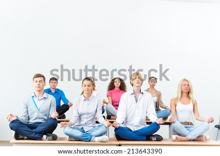 group of young people meditating in office at desk, group meditation - stock photo