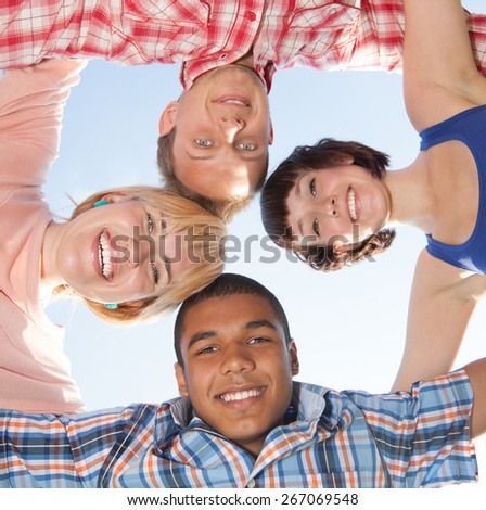 Group of young people outdoor hug each other acrosss blue sky - stock photo
