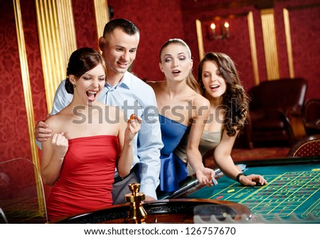 Group of young people playing roulette at the gambling house - stock photo