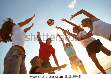 group of young people playing volleyball on the beach - stock photo
