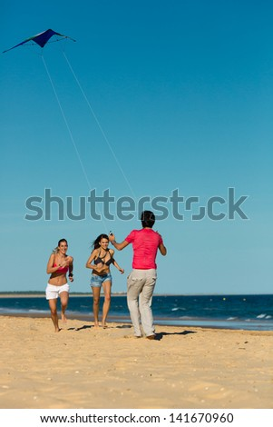 Group of young people playing with a kite on beach in sand outdoors in summer