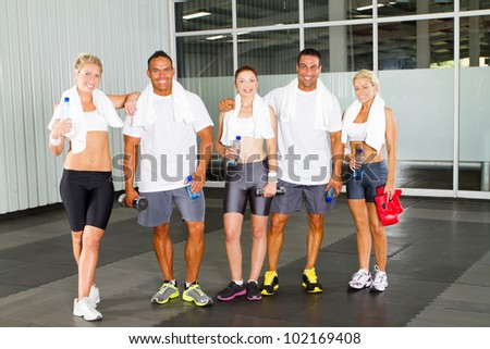 group of young people relaxing in gym after workout - stock photo