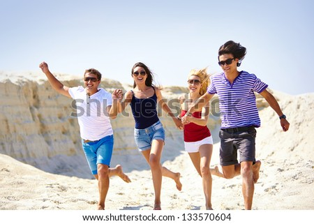 Group of young people running along the beach in summer - stock photo