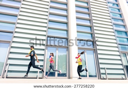 Group of young people running in modern urban area - Fitness girls running with male trainer coach in the city - Sport concept with friends jogging in business center downtown in a sunny bright day - stock photo