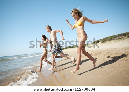 group of young people running into the sea - stock photo