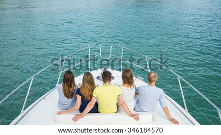 Group of young people siting  and looking outside from yacht. Back view. - stock photo
