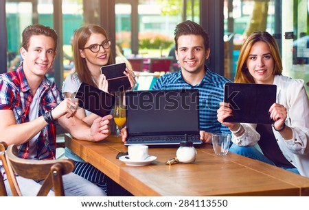 Group of young people sitting at a cafe, holding electronic gadgets - stock photo