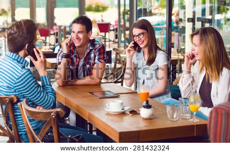 Group of young people sitting at a cafe, talking over mobile phones - stock photo