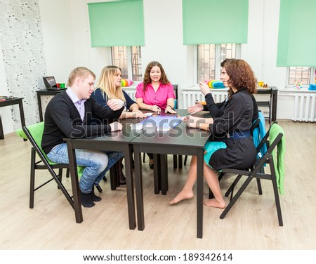 Group of young people sitting at the table and playing games - stock photo