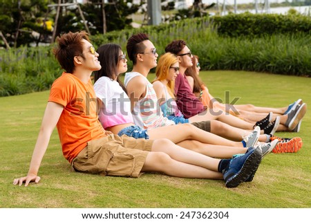 Group of young people sitting on the grass and enjoying the sunlight - stock photo