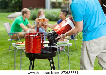 Group of young people spending free time in garden and doing grill - stock photo