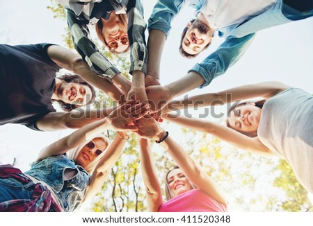 Group of young people standing in a circle, outdoors, having fun