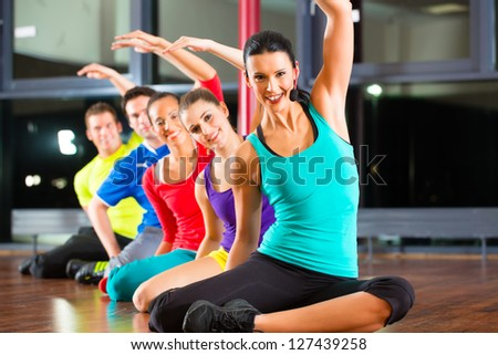 Group of young people stretching in gym for better fitness led by instructor