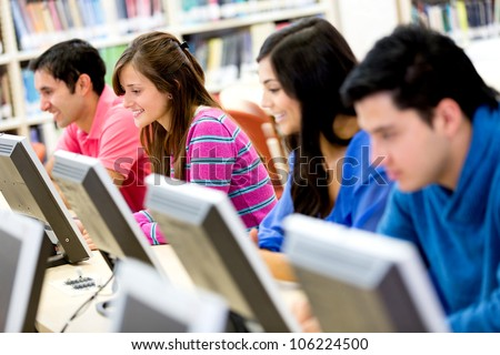 Group of young people studying at the library using computers - stock photo