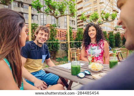 Group of young people talking and laughing around the table with healthy drinks in a leisure summer day outdoors - stock photo