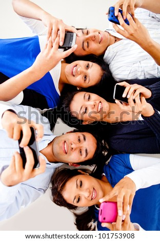 Group of young people texting on their cell phones and smiling - stock photo