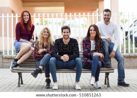 Group of young people together outdoors in urban background. Women and men sitting on a bench in the street wearing casual clothes.