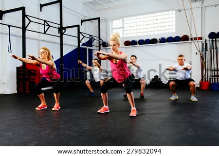 Group of young people training squats at gym class. - stock photo