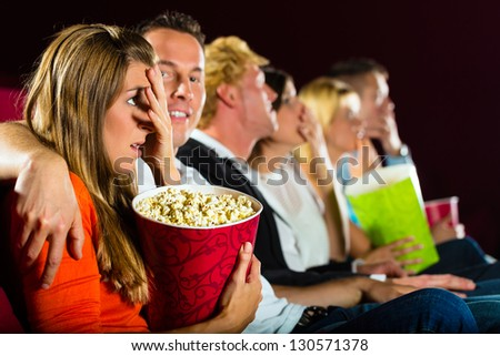 Group of young people watching creepy movie at movie theater - stock photo