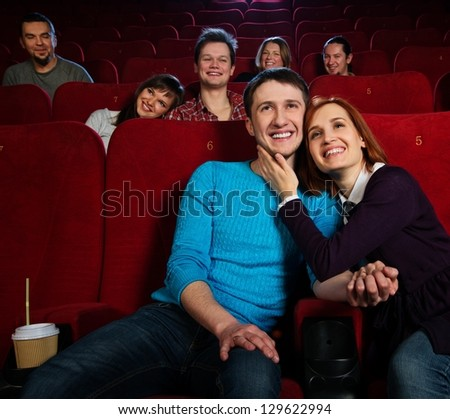Group of young people watching movie in cinema - stock photo