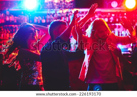 Group of young people with raised arms dancing in nightclub - stock photo
