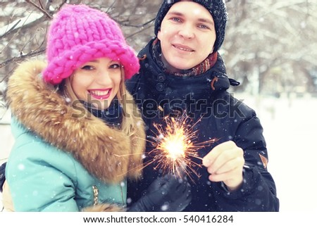 group of young people with sparklers winter