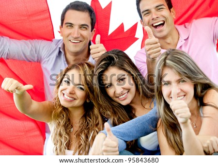 Group of young people with thumbs up and the flag of Canada - stock photo