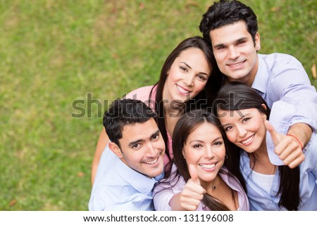 Group of young people with thumbs up outdoors - stock photo