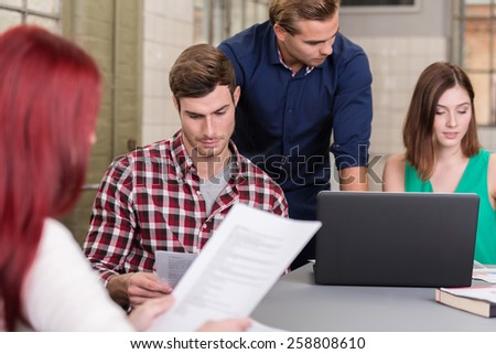 Group of young people working in an office sitting around a table together each engrossed in something different