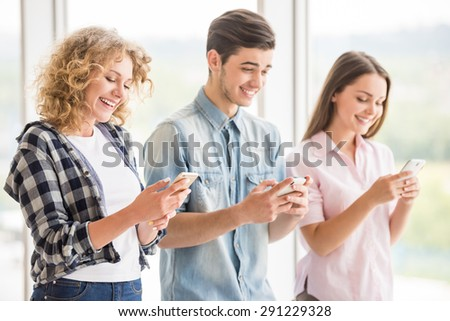 Group of young positive friends using their phones. Education concept. Side view. - stock photo