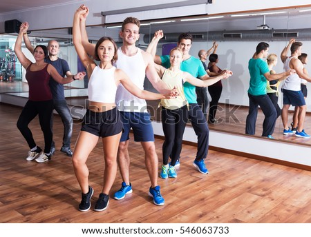Group of young positive people learning salsa at dance class