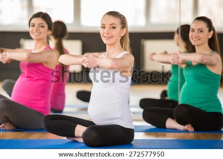 Group of young pregnant women are doing relaxation exercise on exercise mat - stock photo