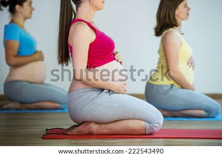 Group of young pregnant women doing relaxation exercise on exercising mat - stock photo