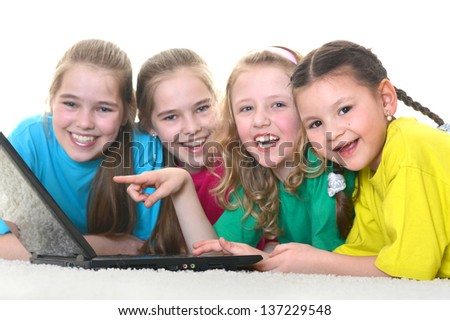 group of young school girls with a laptop on a white background - stock photo