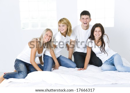 Group of young smiling friends sitting on bed and looking at camera.  Front view.