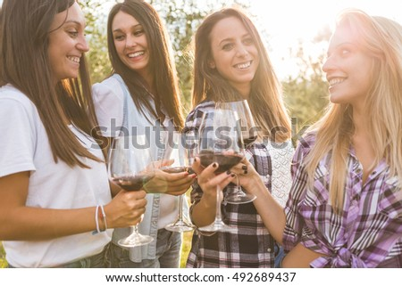 Group of young smiling girls toasting with red wine in wine glasses and enjoying time together in the garden
