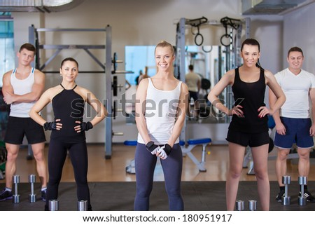 Group of young sport people in gym. Gym and Fitness. Smiling people.