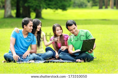 Group of young student using laptop together in the park - stock photo