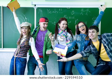 group of young students having fun on the background of the school board - stock photo